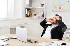Potomstwo relaksujący biznesmen słucha muzykę w nowożytnym białym biurze fotografia stock
