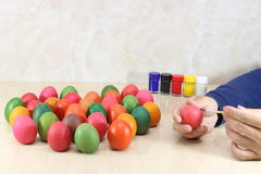 Potomstwo relaksujący mężczyzna maluje Easter jajka z paintbrush na marmuru wierzchołku z kopii przestrzeni tłem Zdjęcia Stock