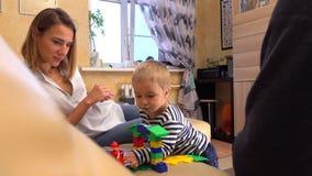 Potomstwo rodzice i ich syn bawić się z kolorową budową ustawiającą wpólnie Linii kolejowej podróży pojęcie 4k strzał zdjęcie wideo