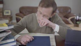 Potomstwo skromnie ubierający mężczyzna spadał uśpiony przy biurkiem w biurze, wiele książki jest na stole Zmęczony i sfrustowany zdjęcie wideo