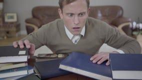 Potomstwo skromnie ubierający mężczyzna spadał uśpiony przy biurkiem w biurze, wiele książki są na stole i na jego głowie _ zbiory