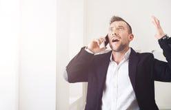 Potomstwo stresujący się biznesmena wezwania telefon komórkowy w nowożytnym biurze zdjęcia royalty free