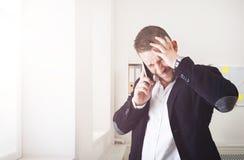 Potomstwo stresujący się biznesmena wezwania telefon komórkowy w nowożytnym biurze zdjęcie royalty free
