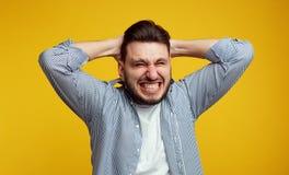 Potomstwo stresujący się młody człowiek zaciska zęby w rozpaczaniu, żałuje o coś, ubiera w błękitnej koszula, odizolowywającej zdjęcie stock
