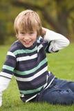 potomstwo target74_0_ siedzących potomstwa chłopiec trawa Zdjęcia Stock