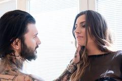 Potomstwo tatuujący mężczyzna dotyka twarz seksowna kobieta Obrazy Stock