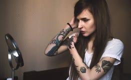 Potomstwo tatuuję kobiety robić uzupełniał przed lustrem Zdjęcie Stock