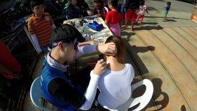 Potomstwo wolontariusz daje młodej kobiecie bezpłatnemu twarz obrazowi w parku zbiory