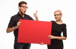Potomstwo zachęcająca para pokazuje prezentację wskazuje plakat Zdjęcie Stock