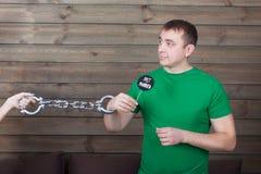 Potomstwo zakładający kajdanki mężczyzna trzyma śmieszną ikonę na kiju Fotografia Stock