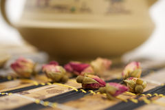 Potpourri and teapot. Chinese traditional clay teapot on bamboo mat and rose buds Stock Images