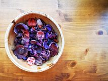 Potpourri of violet, purple and pink flowers and barks inside bamboo bowl on rustic wooden table. stock image