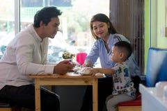 Potrait της ασιατικής οικογενειακής συνεδρίασης μέσα σε έναν καφέ που τρώνε και το κέικ παιχνιδιού που απολαμβάνει την ημέρα στοκ φωτογραφίες
