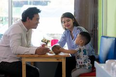 Potrait of asian family sitting inside enjoying the day at cafe. Potrait of asian family sitting inside a cafe eating and playing a cake enjoying the day in the royalty free stock photography
