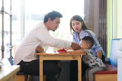 Potrait of asian family sitting inside a cafe eating and playing a cake enjoying the day. In the morning stock images