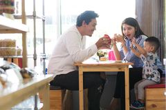 Potrait of asian family sitting inside a cafe eating and playing a cake. Enjoying the day in the morning royalty free stock photography