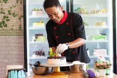 Potrait of asian male pastry chef in a black uniform decorating round vanila cake with melted chocolate and red cherry. At indoors cafe and bakery store stock photos