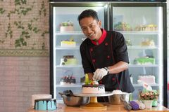 Potrait of asian male pastry chef in a black uniform decorating round vanila cake with melted chocolate and red cherry. At indoors cafe and bakery store stock photo