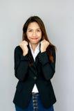 Potrait asiatische Damenshowhandvoll und -lächeln auf grauem Isolat Stockfotografie