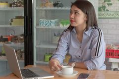 Potrait of a attractive asian women drinking cup a coffee working with laptop and smartphone at a cake store. Potrait of a attractive asian woman drinking cup a royalty free stock image