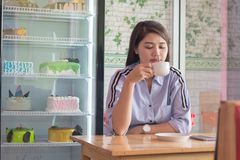 Potrait of a attractive asian women drinking cup a coffee at a cake store. Potrait of a attractive asian woman drinking cup a coffee at a cake store, or cafe in royalty free stock image