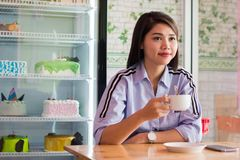 Potrait of a attractive asian women drinking cup a coffee at a cake store. Potrait of a attractive asian woman drinking cup a coffee at a cake store, or cafe in royalty free stock photos