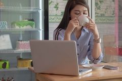 Potrait of a attractive asian women drinking cup a coffee with laptop and smartphone at a cake store. Potrait of a attractive asian woman drinking cup a coffee royalty free stock photos