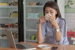 Potrait of a attractive asian women drinking cup a coffee with laptop and smartphone at a cake store. Potrait of a attractive asian woman drinking cup a coffee royalty free stock images