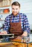 Potrait av den lyckliga skäggiga baristaen på arbete i coffe shoppar Arkivfoto