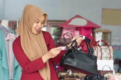 Potrait azjatykciego hijab ?e?ski w?a?ciciel i kostiumer pozycja z czarn? kies? w jej butik mody sklepie, m?ody muzu?ma?ski - wiz zdjęcia stock