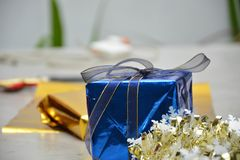 Potrait of a blue gift box on the cement table. With gold ribbon stock photography