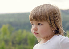 Potrait of a child girl outside. Potrait of a cute but sad looking  child girl, natural outdoor profile portrait Royalty Free Stock Photo
