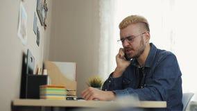 Potrait de los vidrios que llevan del hombre de negocios atractivo joven con el pelo amarillo que habla en el teléfono El sentars almacen de video