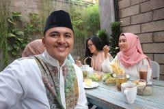 Potrait des moslemischen Mannes Kamera betrachtend während anderes pople Essen stockbilder
