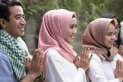 Potrait of a group who getting group of men and women on eid mubarak celebration. Group of young asian indonesian muslim greeting and smiling at outdoor area stock photography