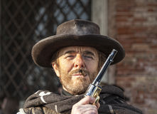 Potrait of a Mercenary. Venice, Italy-February 18, 2012:Environmental portrait of a person with a six-shooter disguised as an old time western mercenary posing Royalty Free Stock Image