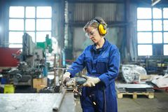 Woman Working in Garage. Potrait of modern female worker cutting metal at industrial plant or garage, copy space royalty free stock photos