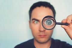 Potrait patrzeje przez powiększać młody człowiek - szkło na białym zamazanym tle Widok męski niebieskie oko przez zdjęcie stock