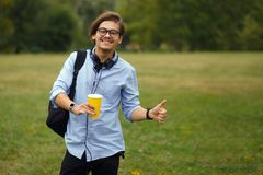 Potrait of student in eyeglass with backpack, holding a cup of coffe and showing thumbs up, on a green park background. stock photography