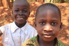Potraite του αφρικανικών χαμόγελου και του παιχνιδιού του χωριού αγοριών κοντά στο σπίτι στο προάστιο της Καμπάλα στοκ εικόνα