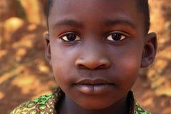 Potraite des afrikanischen l?chelnden Dorfjungen und nahe Haus im Kampala-Vorort spielen stockfotos