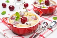 Potrawka (clafoutis) z wiśnią w ramekin, horyzontalnym obraz stock