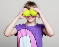 Potrtrait av lite flickan med tennisbollar synar i stället royaltyfria foton