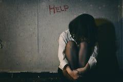 Potrzebuje pomocy, Przygnębionego, sfrustowanego i Smutnego kobiety obsiadanie w ciemnym pokoju, zdjęcie stock