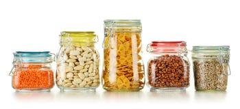 Pots avec des nourritures de grain sur le blanc Photographie stock