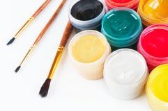 Pots avec les pinceaux colorés de gouache et. Photographie stock libre de droits