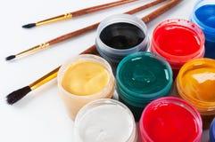 Pots avec les pinceaux colorés de gouache et. Photographie stock