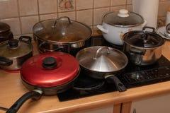 Pots avec les plats cuits sur une cuisine électrique Un désordre sur la table de cuisine photo libre de droits