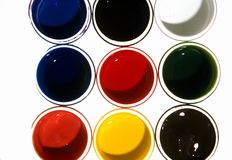 Pots of colors. Colors blue black yellow white orange green in small paint jars pots on white background including the primary colors blur and red and yellow stock photo