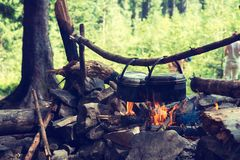 Pots, covered with soot, are hanging over a campfire Royalty Free Stock Photography
